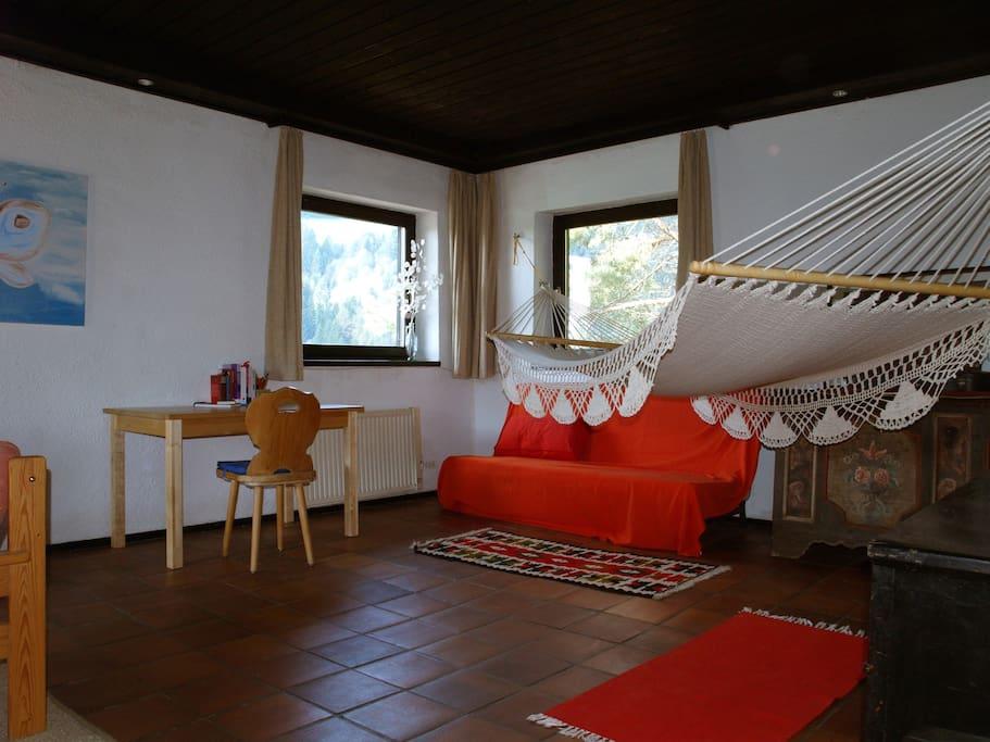Wohnzimmer mit Hängematte - unter der roten Decke verbirgt sich ein Schlafsofa für 2