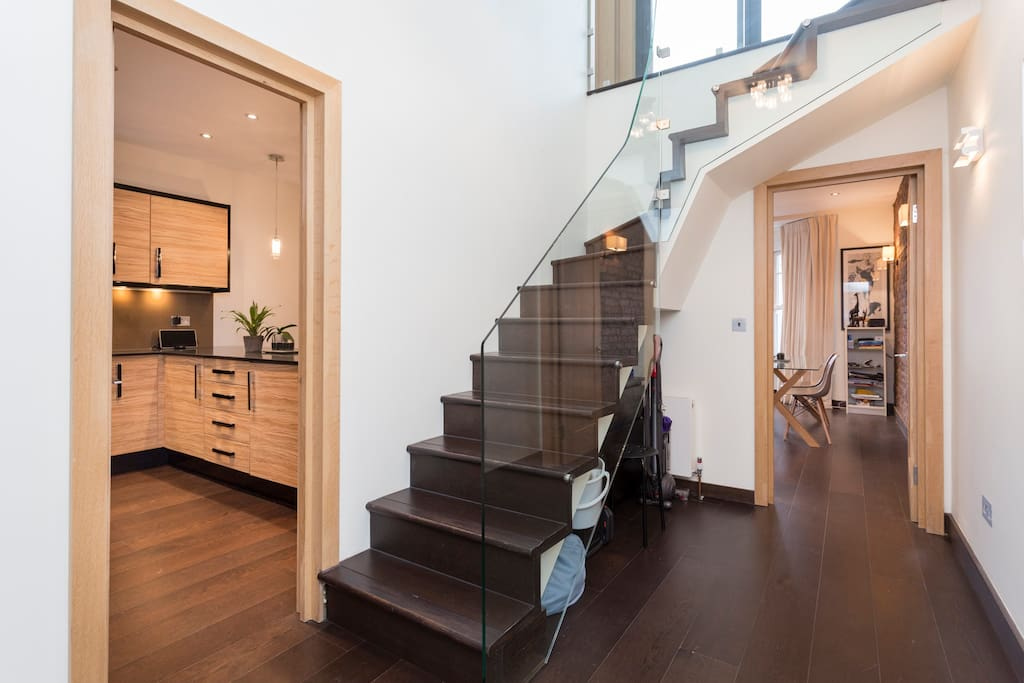 Glass staircase ascending to the master suite