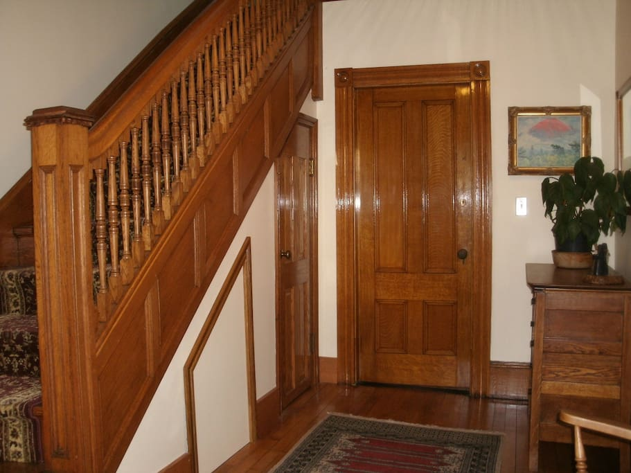 Foyer with oak woodwork, staircase banister and wood flooring.