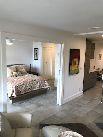 View from living room into the Bedroom with pocket sliding privacy doors that can separate the two spaces for two couples. Each space has a full bathroom
