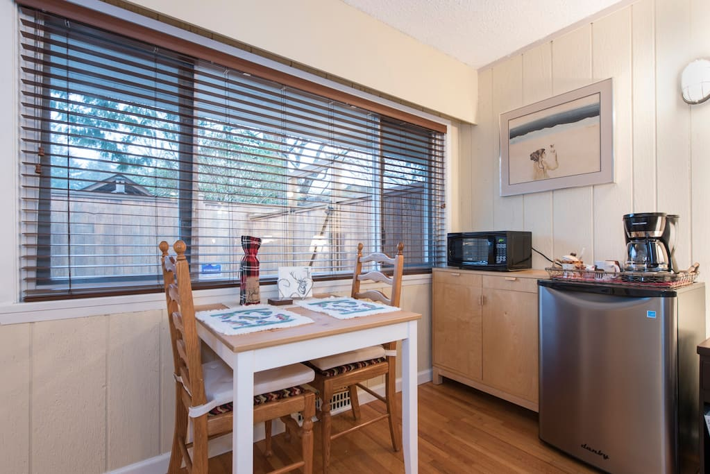 Kitchenette with fridge, microwave, kettle, toaster, dishes and cutlery.