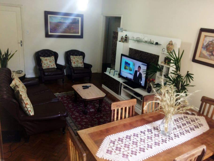Sala de estar.  Sala com mesa de jantar para 6 pessoas, sofás que acomodam ate 5 pessoas, TV ambiente bem iluminado, decorado e agradável.
