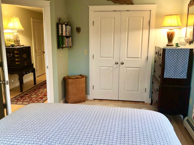 Queen-sized bed with large window--w/shades and curtains to the right--a very cozy room with it's own bathroom very near