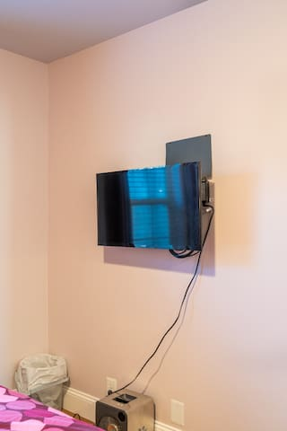 Wall mounted television with HBO, Netflix, ad-free Hulu, and an antenna for over the air content.
