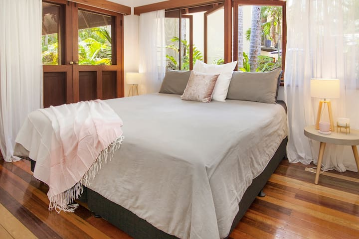 Beautiful master bedroom with luxurious king size bed, looking out onto verandah and gardens