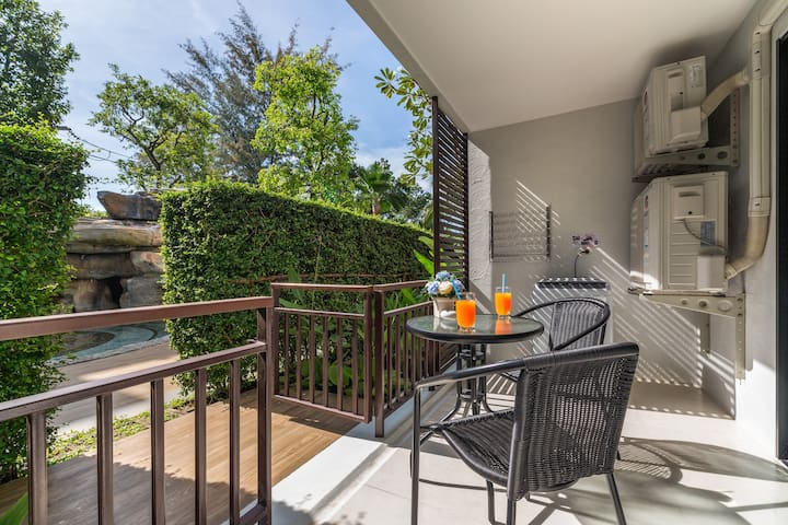 Balcony with pool access and outdoor furniture to enjoy the green garden view