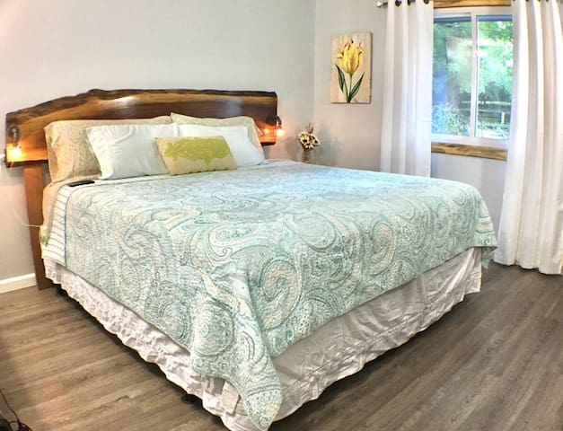 King size Sealy Posturpedic memory foam mattress featuring a custom live edge walnut slab headboard with built in outlets and reading lamps.