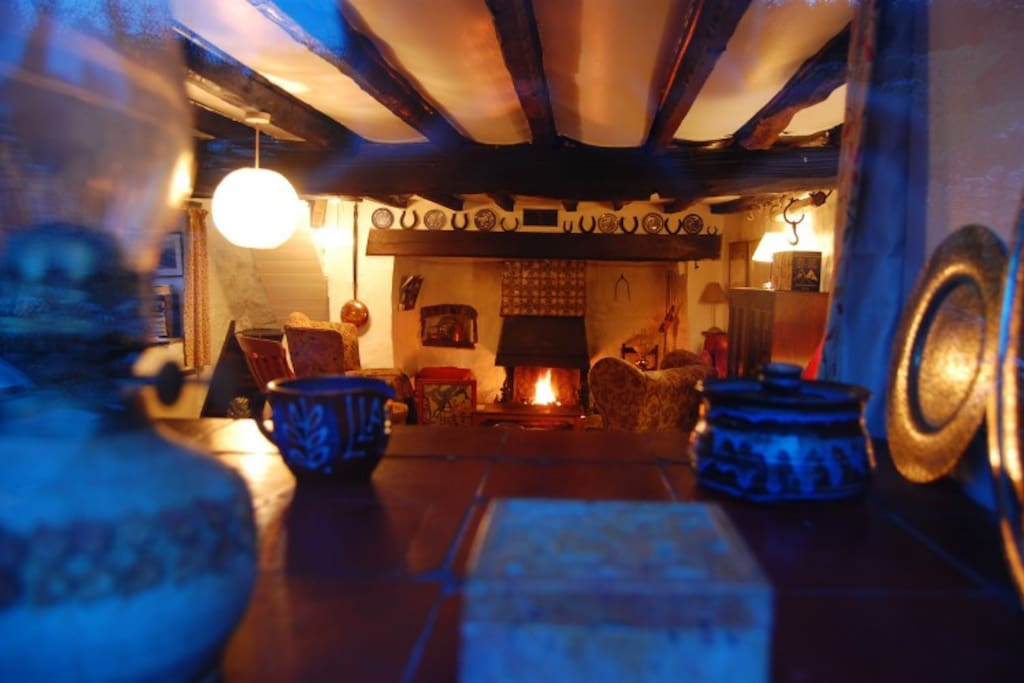 This is the living room of the cottage with the log burning stove at the centre of the enormous fireplace