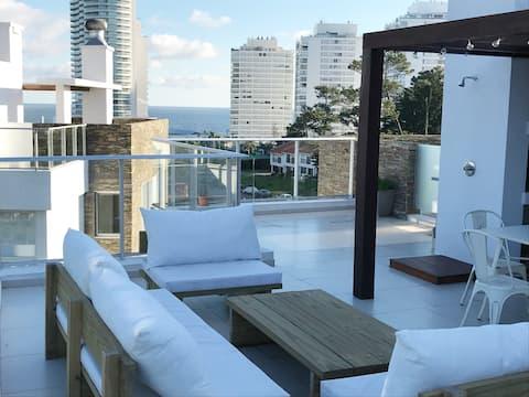 Estudio en terraza con parrillero y vista al mar