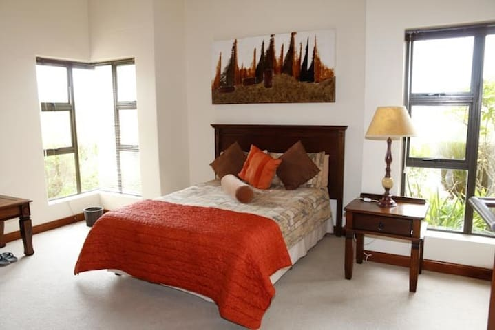 Large bedroom 3 with a double bed and en-suite bathroom, including a bath, vanity and toilet