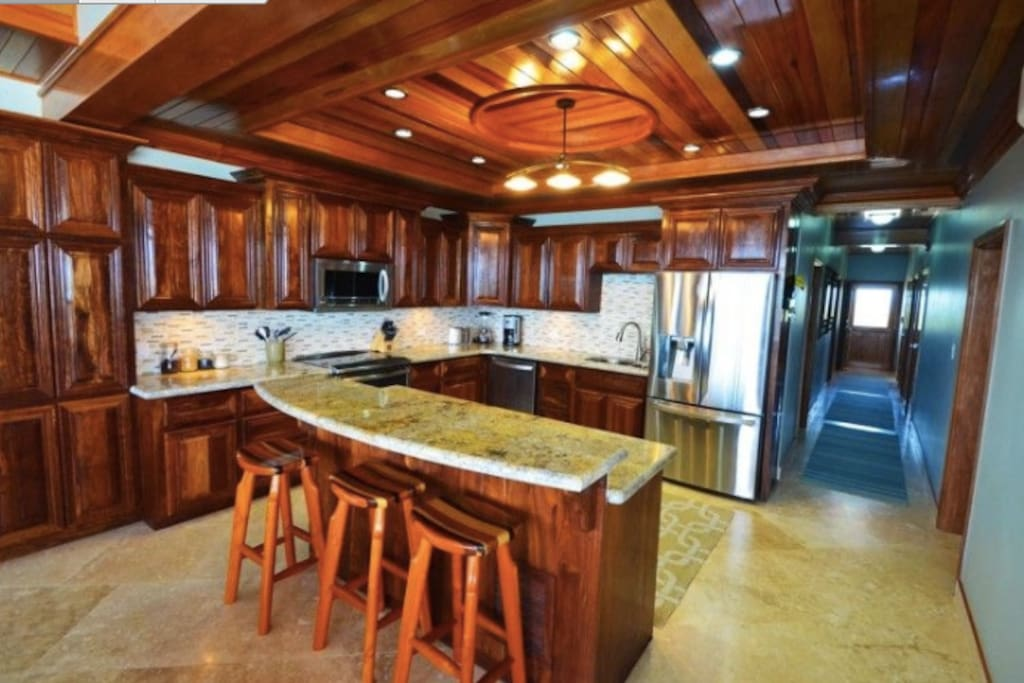 Fully stocked gourmet kitchen with stainless appliances, granite counters, and gorgeous Belizean hardwood cabinets!