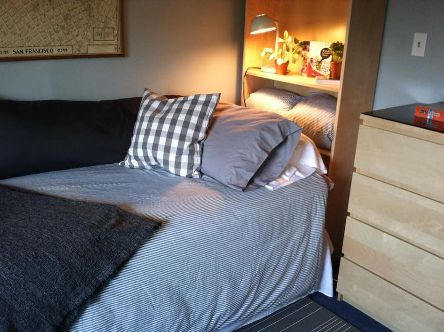 Cozy American twin (single) bed with excellent reading light. A folding bed tray is stored next to the bed.