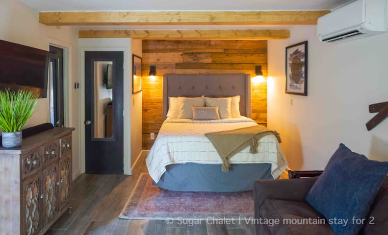 Cozy bedroom with West Elm bedding, luxury memory foam mattress, and modern-rustic details.  The bedroom is open to the living area and looks out onto the patio.