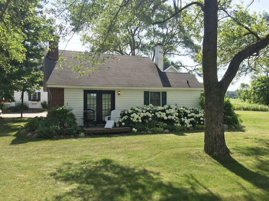 You can see the main house behind the cottage.  It shares the driveway.  However, the side yard is completely reserved for the use of the cottage guests.  They are about 50 feet apart.