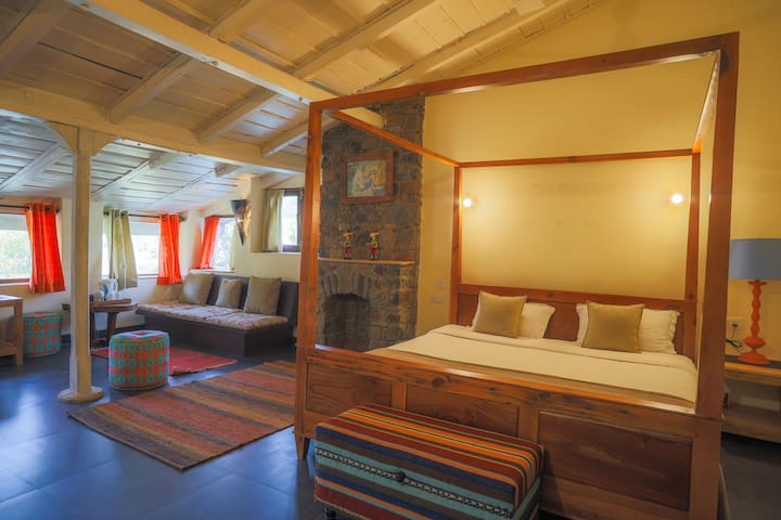 A luxury suite room with poster beds, electronic bed, and Tea kettle