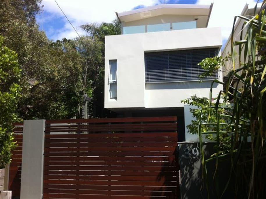 Front of house, view from street, master suite balcony on top floor, electric swing gate in foreground.