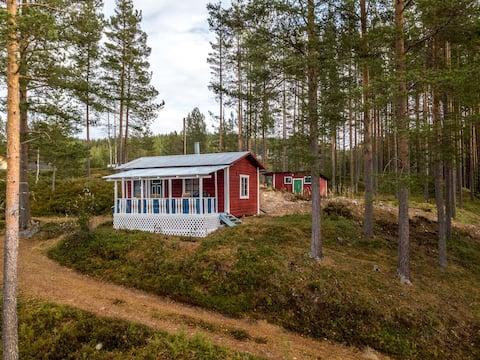 Idyllisk tømmerhytte ved innsjøen Storsjøen.