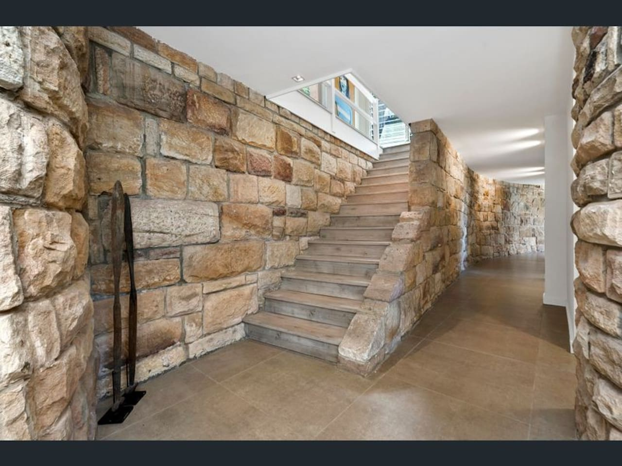 Second level of home with stunning, curved sandstone feature walls & gallery hallway leading to bedrooms & bathroom.