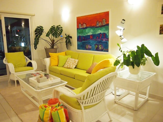 Living TV area with another of my paintings. A lovely monstera plant adorns the corner.