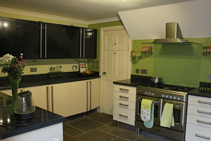 Stone floored kitchen with gas range cooker and dual ovens.