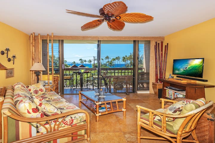 Living area has cozy tiki-style furnishings, including a pull-out couch, ceiling fan, and air conditioner