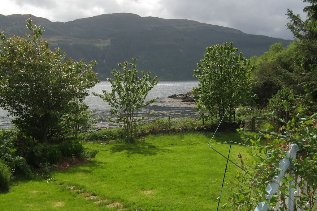 A view from the bedroom window. The steps into the garden and the gate leading to the shore can be seen to the right
