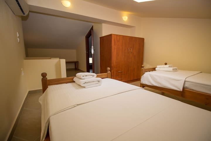 loft with two single beds and a separate bathroom with a shower cabin