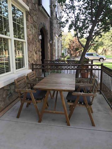 Nice patio with patio furniture on the front porch to eat outside with a yard in front