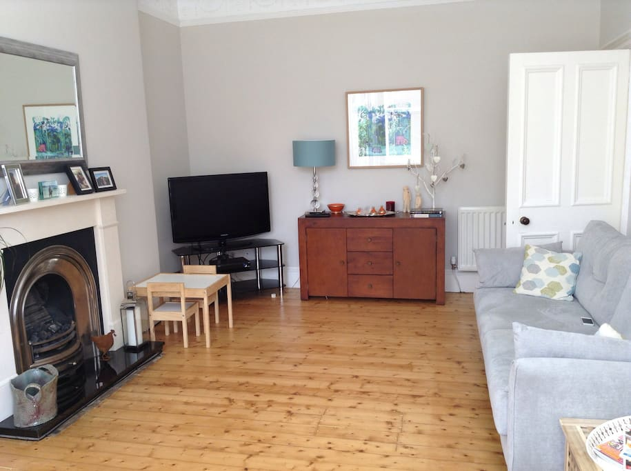 Large Living room with gas fire place and wooden floor boards