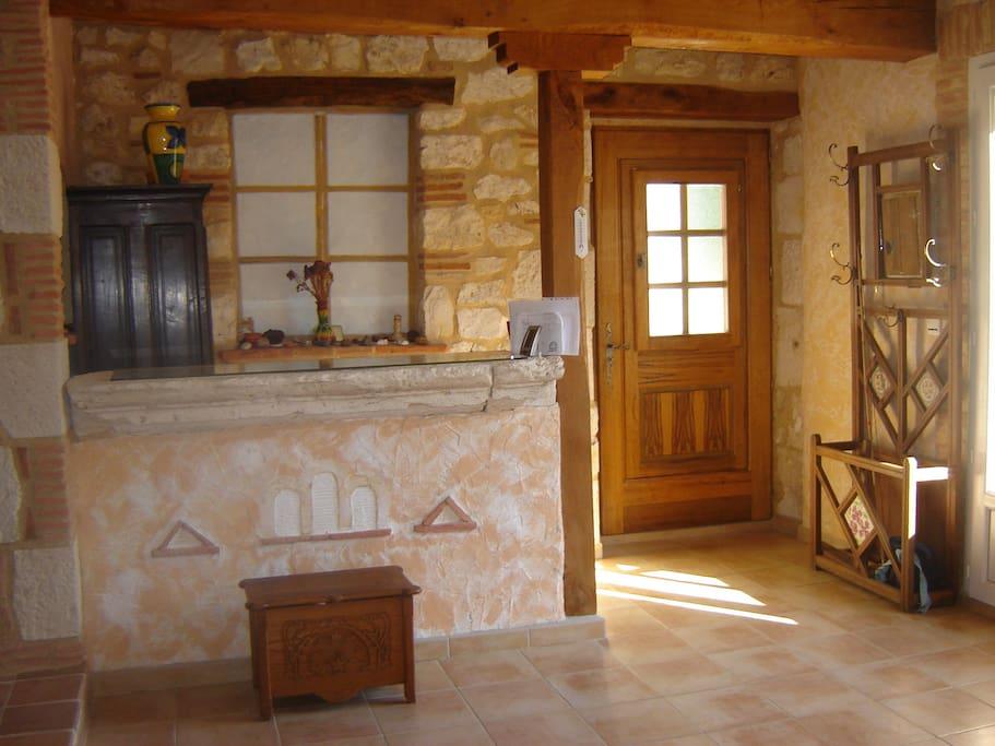 Un hall d'entrée spacieux et lumineux avec un accès direct au jardin et à la cuisine
