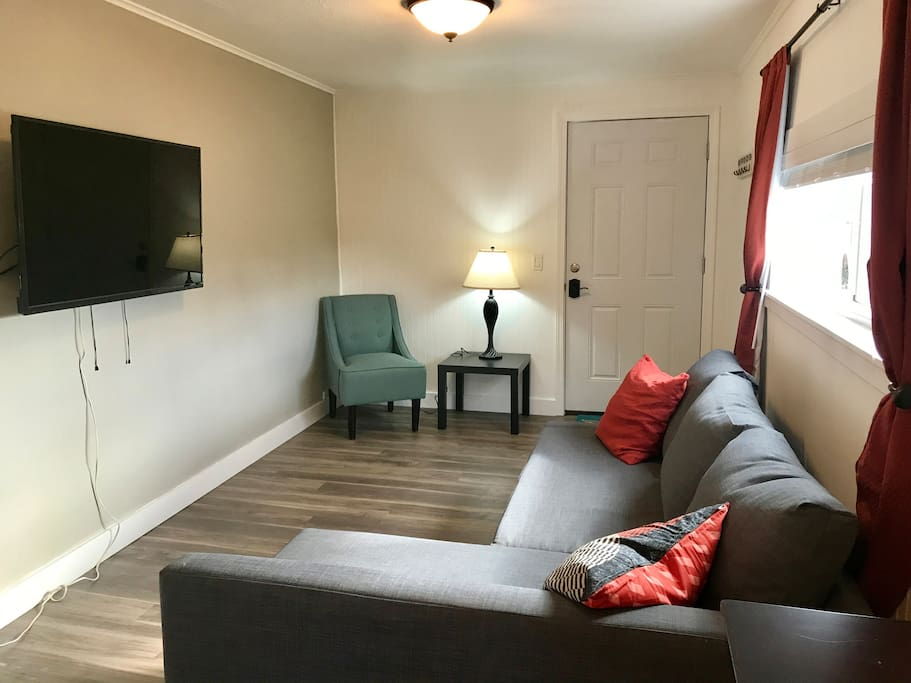 Light-filled living room features flat screen TV with premium cable, extremely comfortable fold out couch.