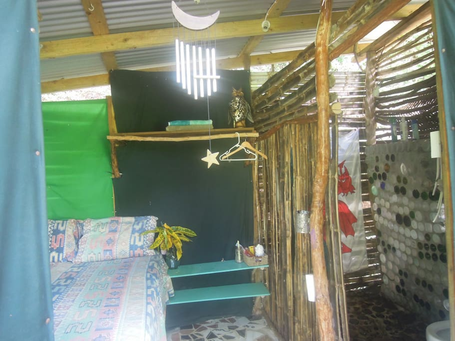 Made from Fiddle wood and Bamboo, small cozy and private, Colorful Fabric covers the wall, re-cycled tiles, river stone floor and shower walls made from re-cycled rum and wine bottles.