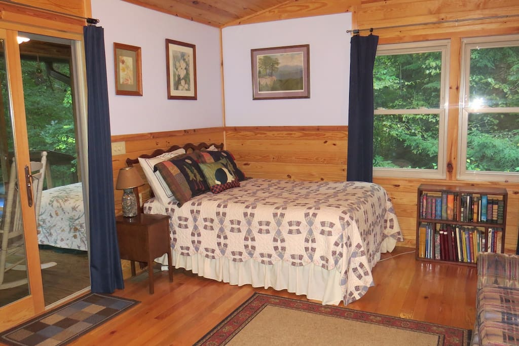 Double bed, oak flooring with area rugs, local paintings