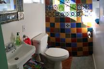 The private half bath has its own burst of color.