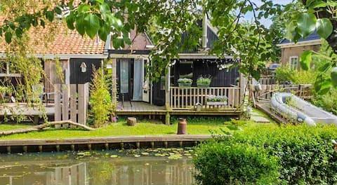 Uniek houten huisje aan het water.