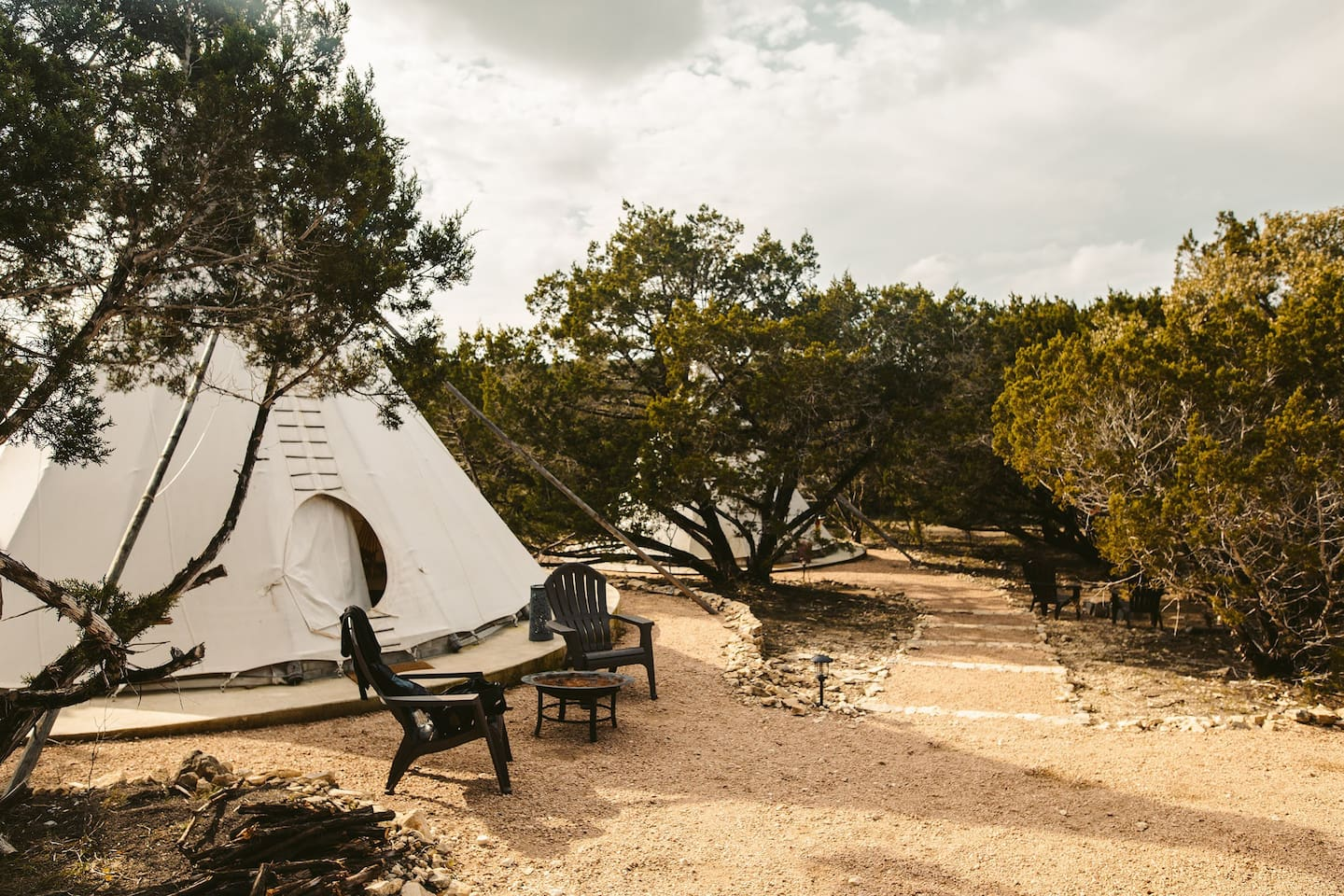 Tipi La Estrella with its private fire pit and two outdoor chairs. To the right, down the steps is tipi La Rosa.