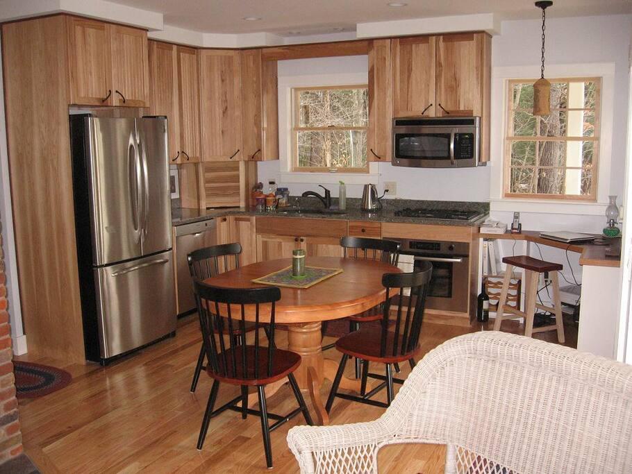 Bright, modern cottage kitchen features gas range and dishwasher.