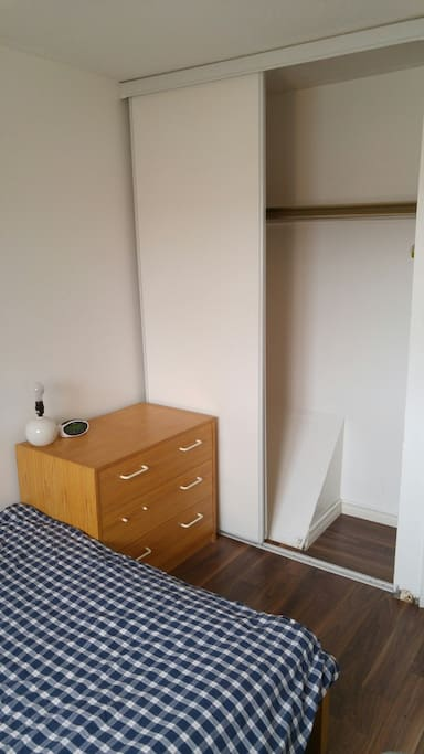 Bedroom with double-sized bed, desk, chair, dresser, lamp and closet