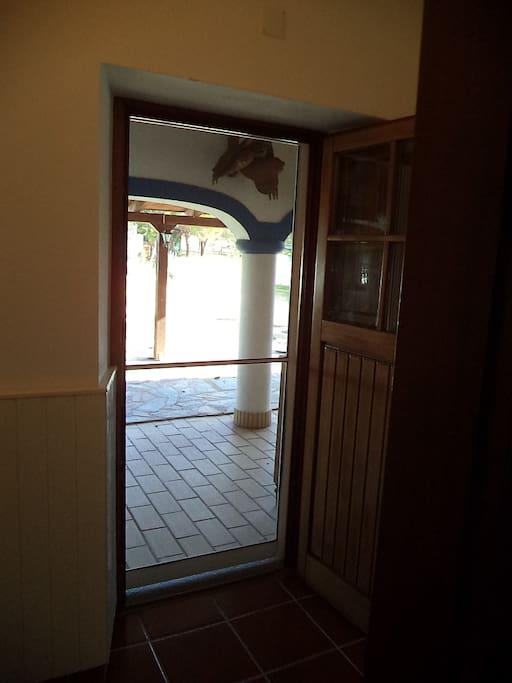 Entrada com porta dupla em madeira e porta rede de mosquiteira.
