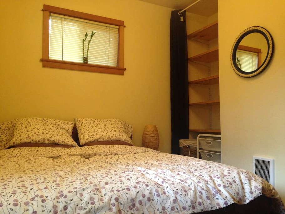 Separate bedroom with queen bed with new linens, lots of storage, funky bicycle tire mirror and separate heater.