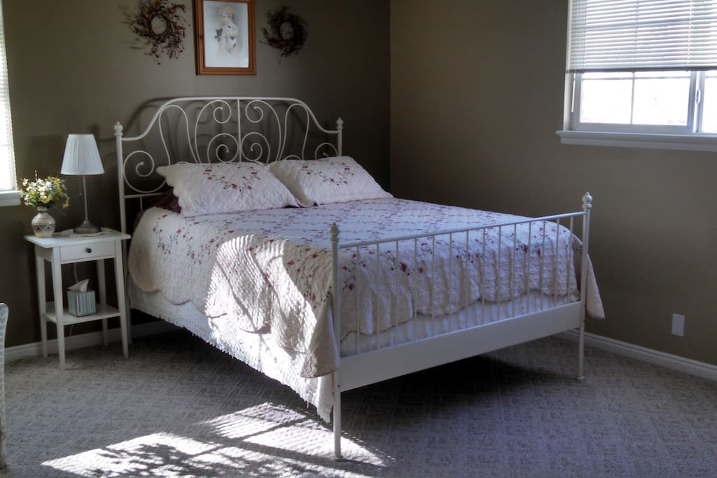This bedroom features vintage style queen bed, dresser and walk in closet.