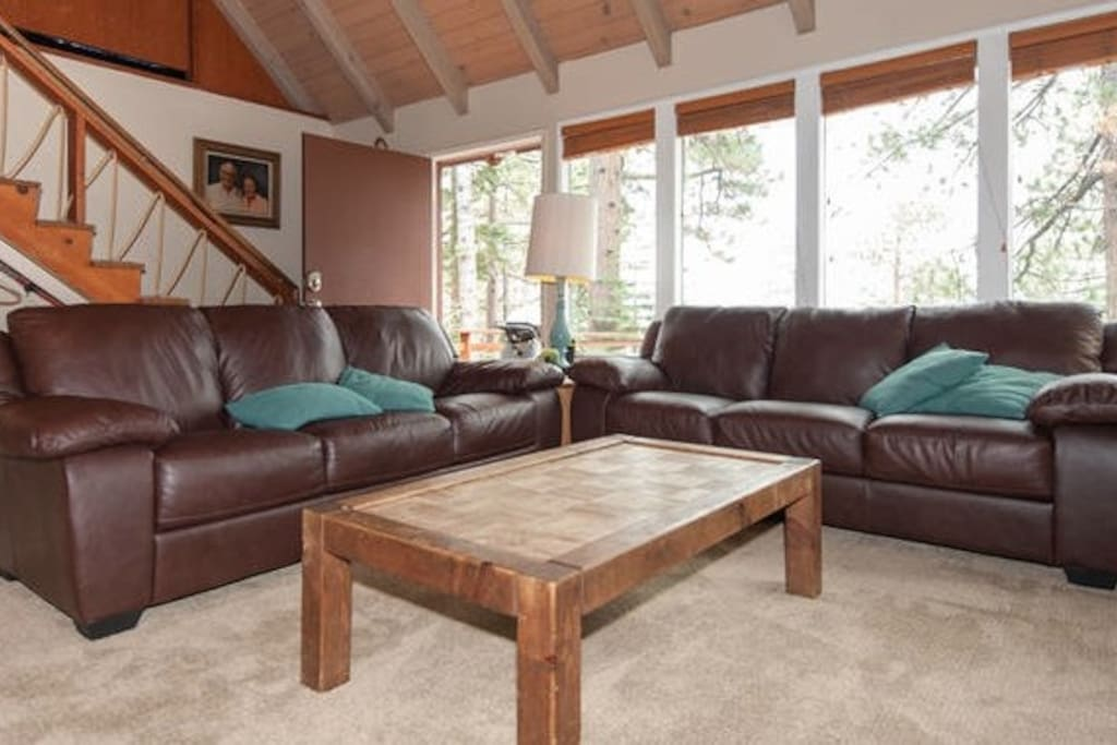Spacious living room with wide open views of Lake Tahoe and pine trees. Brand new leather couches and new carpet