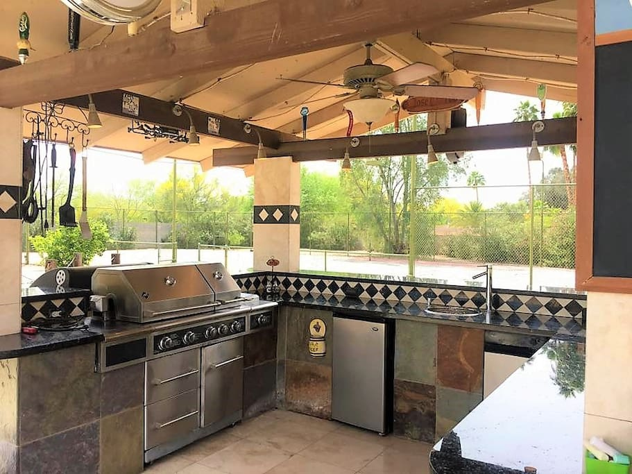 Outdoor kitchen with built in propane grill, sink, fridge, and beautiful night lighting. Unattached charcoal grill provided to accommodate your preference as well.