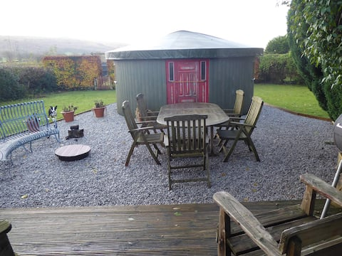The Yurt, fire pit, and table, in a private corner of the garden