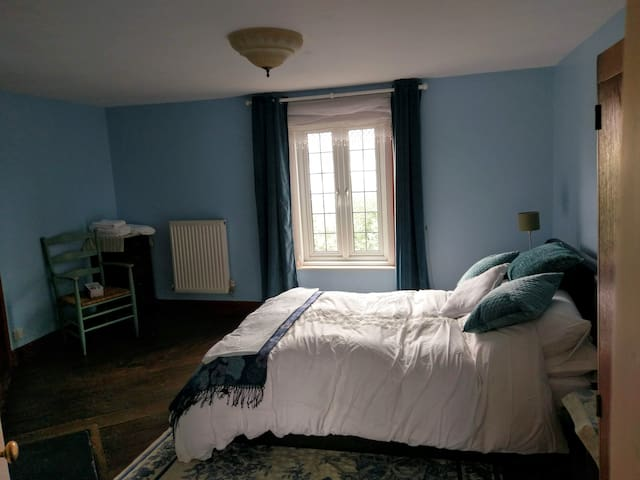 Bedroom with double bed, wardrobe, mirror, drawers and en suite off with bath and shower over