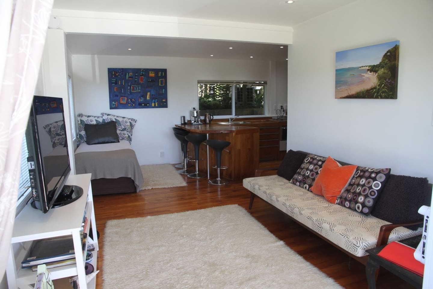 Open plan living area looks out to the sea. Showing breakfast bar, single bed and sofa bed.