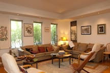 Living room filled with original art and musical instruments including a Steinway upright piano