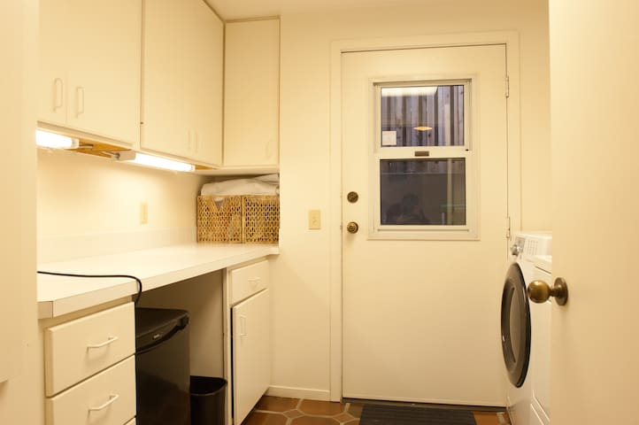 Laundry with washer dryer, fold down ironing board, guest fridge, microwave, kettle