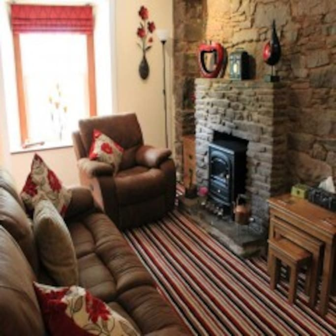 Comfortable sitting room with original stone wall.