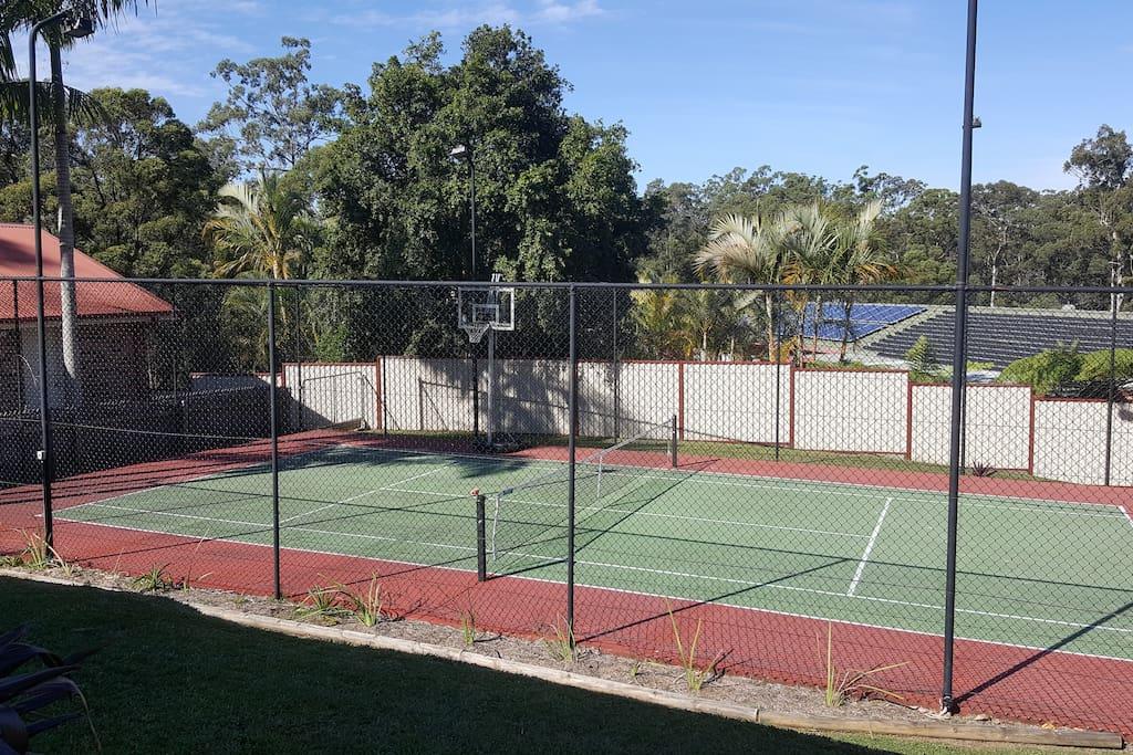 Half tennis court, balls and rackets provided.  Basketball hoop.